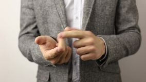 Solid caucasian man in gray jacket and speckled shirt on white background counting on fingers till five fast. Businessman counts till five bending his fingers stock footage