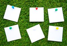 Solid color notes, isolated on artificial grass background royalty free stock photo