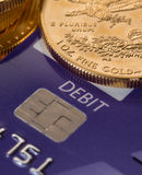 Gold coins on chip and pin debit card. Solid gold coins contrasted with debit word on plastic credit card suggesting debt problems royalty free stock image