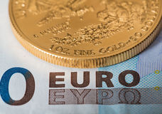 Gold coins on euro note bill with coins Stock Image