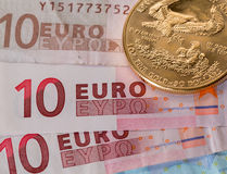 Gold coins on ten and twenty euro notes bills. Solid gold coins contrasted with numbers on euro note suggesting debt problems stock image
