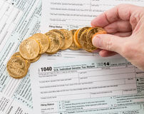 Solid gold coins on 2014 form 1040 Royalty Free Stock Photo