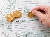 Solid gold coins on 2014 form 1040 Royalty Free Stock Images