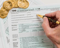 Solid gold coins on 2014 form 1040 Stock Photography