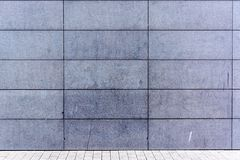 Solid grey wall. Solid grey rock wall and pavement Stock Photography