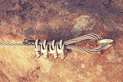 Solid knot on steel rope. Iron twisted rope fixed in block by screws snap hooks. Detail of rope end anchored into sandstone rock Royalty Free Stock Photos