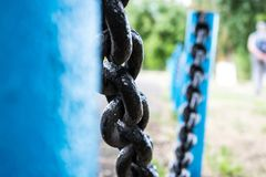 Solid and large metal black chain on the fence with blue pipes, base. royalty free stock images