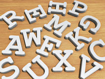 Solid letters. White solid letters on wood table background Stock Photo