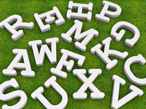Solid letters. White solid letters on grass ground background Stock Image