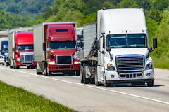 A solid line of eighteen-wheelers barrel down an interstate highway in Tennessee. Heat waves rising from the pavement give a nice shimmering effect to Stock Images