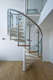 Solid newel stairs with wooden steps. And glass and steel rail Stock Images