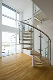 Solid newel stairs with wooden steps. And glass and steel rail Stock Photos