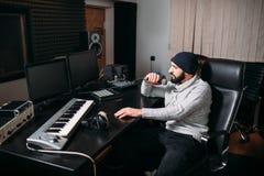Solid producent med mikrofonen i musikstudio Fotografering för Bildbyråer
