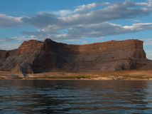 Solid Rock. A solid rock plateau looms above the beach of the lake Stock Images