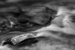Solid Rock. Rock surrounded by flowing water in stream Royalty Free Stock Image