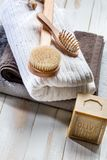 Solid soap, body brush, hairbrush and towels for green bath. Eco-friendly home spa still life with big traditional solid soap, body brush, hairbrush and pile of Royalty Free Stock Photos