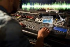 Solid tekniker på den blandande konsolen för inspelningstudio fotografering för bildbyråer