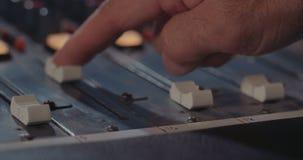 Solid tekniker som justerar en blandande konsol i en inspelningstudio arkivfilmer