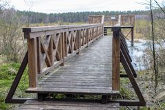 A solid wooden bridge over the forested wetlands. Forest reserve of forest bogs. Season winter stock images