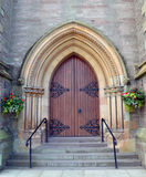 Solid wooden entrance door, St Matthews Church, Perth, Scotland. Wooden door, with hanging flower baskets to either side, on St Matthews Church, Tay Street royalty free stock image