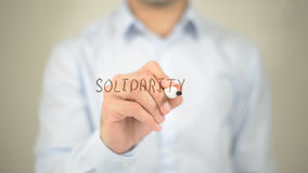 Solidarity , man writing on transparent screen Stock Image