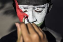 Solidarity for Palestine. A man paint his face with Palestine Flag to show his solidarity for Palestine Stock Photos
