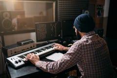 Solide Produzentarbeit mit Audiogeräten im Studio Stockfotografie