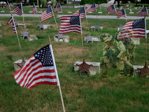 Solider kneeling in cemetery stock photo