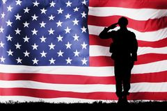 Solider Silhouette With American Flag. Silhouette Of A Solider Saluting Against The American Flag Stock Image