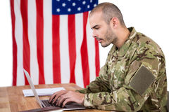 Solider using a laptop at desk Stock Photography