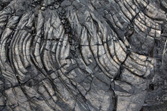 Solidified black lava rock. Patterns cracks and shapes emerge from this close up portion of black solidified lava on the island of Hawaii royalty free stock photography