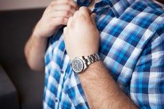 Solidny mężczyzna w błękitnej szkockiej kraty koszula z krótkim rękawem i zegarku na jego nadgarstku zapina kołnierz zdjęcia royalty free