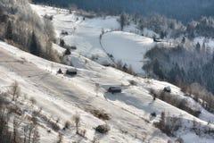Solig dag av en vinter, på lösa transylvania kullar med Bucegi berg i bakgrund Arkivfoto