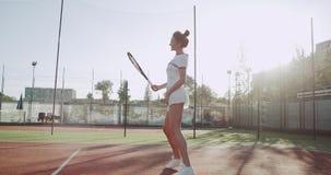 Solig dag för tennisbana, en nätt dam som utrustas för att flytta sig för tennislek som är roligt för leken lager videofilmer