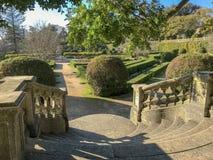 Solig dag i formell trädgård med topiaryväxter, släta linjer, geometrisk form, raunded trappa och spår i Lissabon royaltyfria bilder