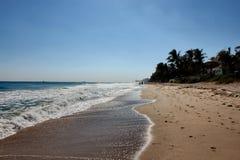 Solig dag på en Florida strand med vågor och fotspår arkivfoto