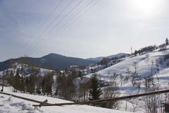 Solig dag sikt från fönstret på ett snöig vinterlandskap Bergby, hus och staket royaltyfria foton
