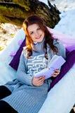 Solig dag, vinter, skog och kvinna med boken Royaltyfri Bild