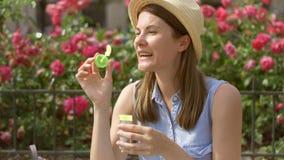 solig dagsommar Ung rolig flicka som blåser luftsåpbubblor Den härliga rosa färgen blommar på bakgrund lager videofilmer