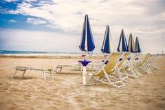 Solig Italien sandstrand Adriatiskt hav riviera Blåa och gula solstolar arkivfoton