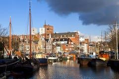 Solig kanal i Groningen med många flodfartyg royaltyfria foton