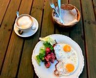Solig sida upp ägg med bacon och grönsaker och kaffekoppen Fotografering för Bildbyråer