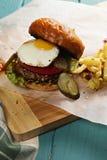 Solig sida upp hamburgaren på en trätabletop Royaltyfria Bilder