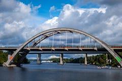 Solig sommarsikt av en välvd konkret drevbro med himmel, vatten och fartyg fotografering för bildbyråer