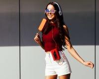 Solig stående av en asiatisk flicka i en moderiktig sommardräkt, en hörlurar, en trendig solglasögon och en tappningkassett Arkivbild