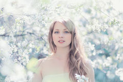 Solig stående av en härlig kvinna i en blomningvår Royaltyfri Foto