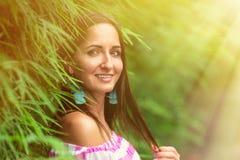 Solig stående av en härlig kvinna nära ett grönt staket arkivfoto