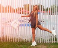 solig stående Skönhet med långt hår med en sporthandväska som poserar på en varm afton barnfadergyckel som har att leka tillsamma Arkivbilder