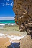 Solig strand med en klippa i förgrunden arkivfoton