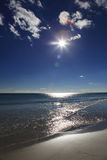 Solig strand med sand, vågor, moln och blå himmel Arkivfoto